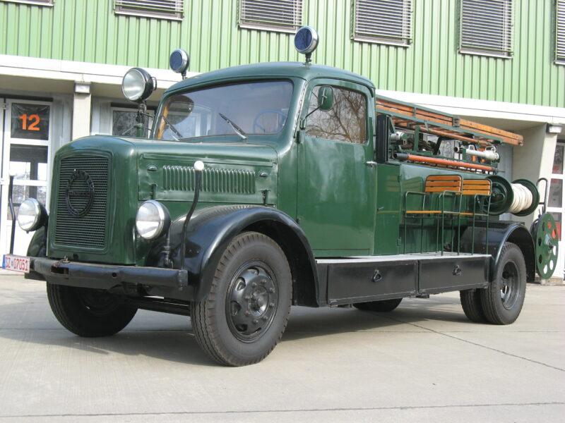 """Das Bild zeigt das TLF 15 aus dem Jahr 1941. Ab dem 31. Juli 1940 gebaute Feuerwehrfahrzeuge waren in der Farbe """"Tannengrün"""" lackiert. Das hing damit zusammen, dass die von 1938 bis 1945 """"Feuerschutzpolizei"""" genannte Feuerwehr organisatorisch der Polizei unterstellt war, deren Farbe das Tannengrün war. So hatten die Angehörigen der Feuerschutzpolizei ab 1939 auch grüne Polizeiuniformen."""